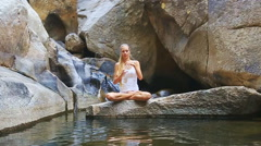 Blond Girl Sits in Pose Lotus on Stone Returns Water Bottle Stock Footage