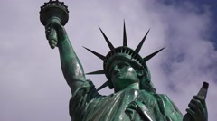A patriotic shot of the Statue Of Liberty against a cloudy sky with the American Stock Footage