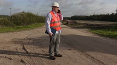 Angry engineer with folder talking on phone on the rural road Stock Footage