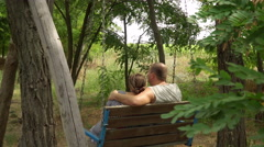 Man and woman swaying in the a bench among the trees Stock Footage