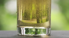 Slow motion 180fps beer poured into the glass on stone board with green nature Stock Footage