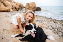 Cheerful woman hugging her dog on the beach Stock Photos
