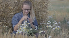 Girl sitting in the straw stack and guesses on camomile Stock Footage