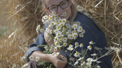 Girl in a field near the stacks of straw with a bouquet of white daisies Stock Footage