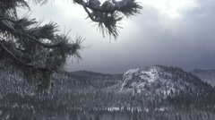 Clouds and fog move over a beautiful snow scene in winter in the high Sierra Stock Footage