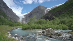 River and glacier in the mountains - Briksdale glacier, wild scenery, Norway Stock Footage
