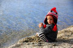 Little girl is sitting on sandy beach and trying to take the shues off. Lake  Stock Photos