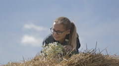 Girl lying on a stack of straw with a bouquet of white daisies Stock Footage