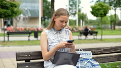 Student texting on smartphone while studying on laptop in the bench Stock Footage