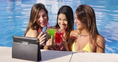 Three bikini clad friends toasting pool side Stock Footage