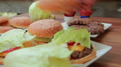 Hands placed on top of the hamburger buns Stock Footage