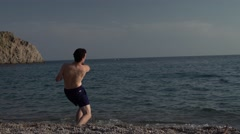 Boy Skipping Stones in the Sea 4K Stock Footage