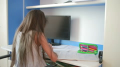 Schoolgirl doing homework at the table leafs through book. Girl makes lessons Stock Footage