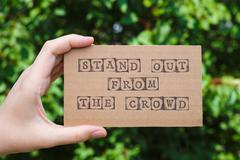 Hand holding card with phrase Stand Out From The Crowd Stock Photos