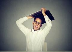 Furious nervous business man about to smash throw his laptop computer Stock Photos