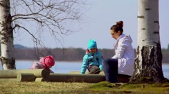 Charming family of three playing in the sandbox on a spring day Stock Footage