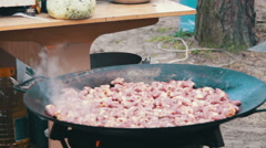 Cooking Meat in a Cauldron over an Open Fire Outdoors Stock Footage