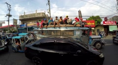 Passengers ride dangerously atop a jeepney Stock Footage