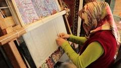 Muslim woman weaving handmade silk carpet Stock Footage