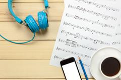 Top view music sheet note paper,headphones,smartphone,pencil,coffee on wood Kuvituskuvat