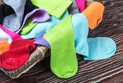 Scattered multi-colored socks and laundry basket Stock Photos