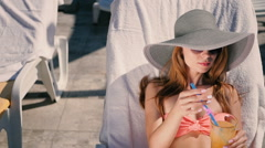 The girl drink a cocktail near the swimming pool Stock Footage