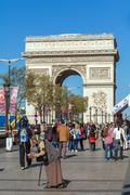 PARIS, FRANCE - APRIL 7, 2011: People walking in front of Arc de Triomphe Stock Photos