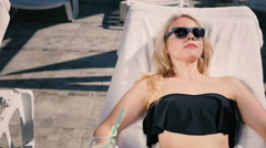 The blonde drinking coctail near the swimming pool Stock Footage