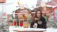 Beautiful young woman using a smartphone and drinking hot tea during the Stock Footage