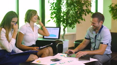 Three colleagues communicate looking at documents in folders sitting in the Stock Footage