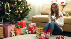 Young beautiful girl wrapped the Christmas gift Stock Footage