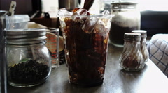 Barista mixing coffee with fresh milk on ice, 4K Stock Footage