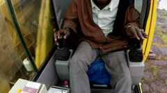 Camera inside the control cabin of a crane. The driver is of African ethnicity. Stock Footage