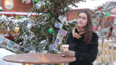 Beautiful young woman drinking hot tea during the Christmas Fair Stock Footage