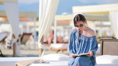 Young woman reading book during tropical beach vacation. Fashion girl read Stock Footage