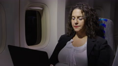 Woman using her laptop on an airplane Stock Footage