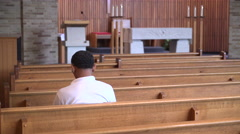 Sad man sits alone praying in a church Stock Footage
