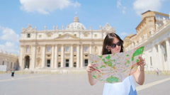 Happy young woman with city map in Vatican city and St. Peter's Basilica church Stock Footage