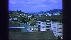 1963: scenic view of a small city set against a beautiful backdrop of mountains Stock Footage