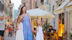 Happy mother and little adorable girls on cozy street during italian vacation Stock Footage