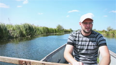 The man rowing the oars on the river on a wooden boat Stock Footage