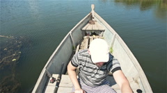 The man vigorously rowing oars on the river on a wooden boat Stock Footage