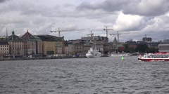 Red pleasure boat heads to Gamla Stan as seen from a moving ferry Stock Footage