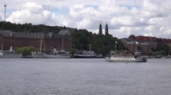 Old ferry in grey livery approaches pier in Sodermalm with industrial background Stock Footage