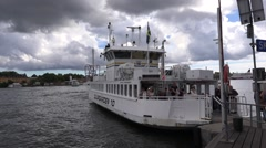 Passengers board the Djurgarden ferry and it departs from Skeppsholmen pier Stock Footage