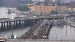 Two different metro trains travel on parallel tracks along bridge in Slussen Stock Footage
