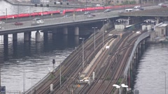 Metro (Tunnelbana) and red MTR train travel along bridges in Slussen Stock Footage
