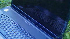 Laptop lying on the grass in the park - lay down glasses on laptop Stock Footage