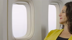 Woman looking out the window of an airplane, smiling, close up shot Stock Footage