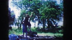1959: young woman swinging on a rope swing under the shade of a group of trees Stock Footage